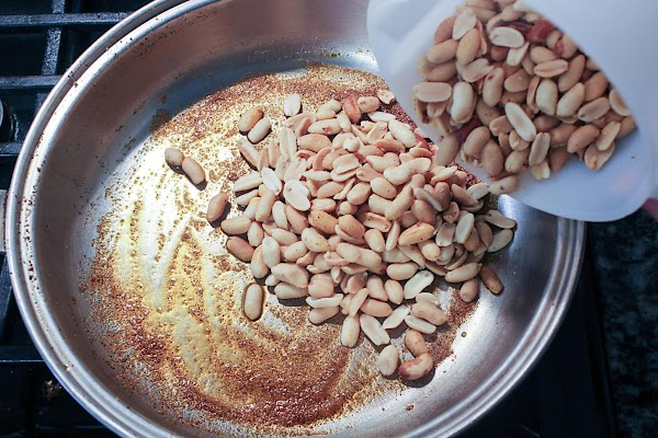 Peanuts added to spices in saute pan.