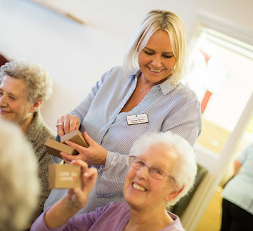 a carer smiling while handing out tools for residents