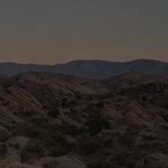 Sun setting over a desert landscape