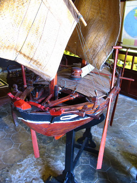 """Photo: Details of the bow, showing the """"nga"""" or ornamental anchor line fairlead and the pair of wooden anchors just behind it.  The hardwoods in Viet Nam include some that are denser than water and thus sink, though using stones attached to the anchor and the anchor line was common even when the wood would sink of its own.  The pattern of the eyes is the same as still used on traditional boats from Hoi An."""