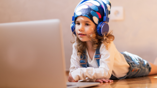 image of young girl with headphones looking at laptop