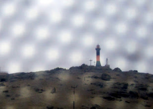 Photo: lighthouse through the screened windows on the bus