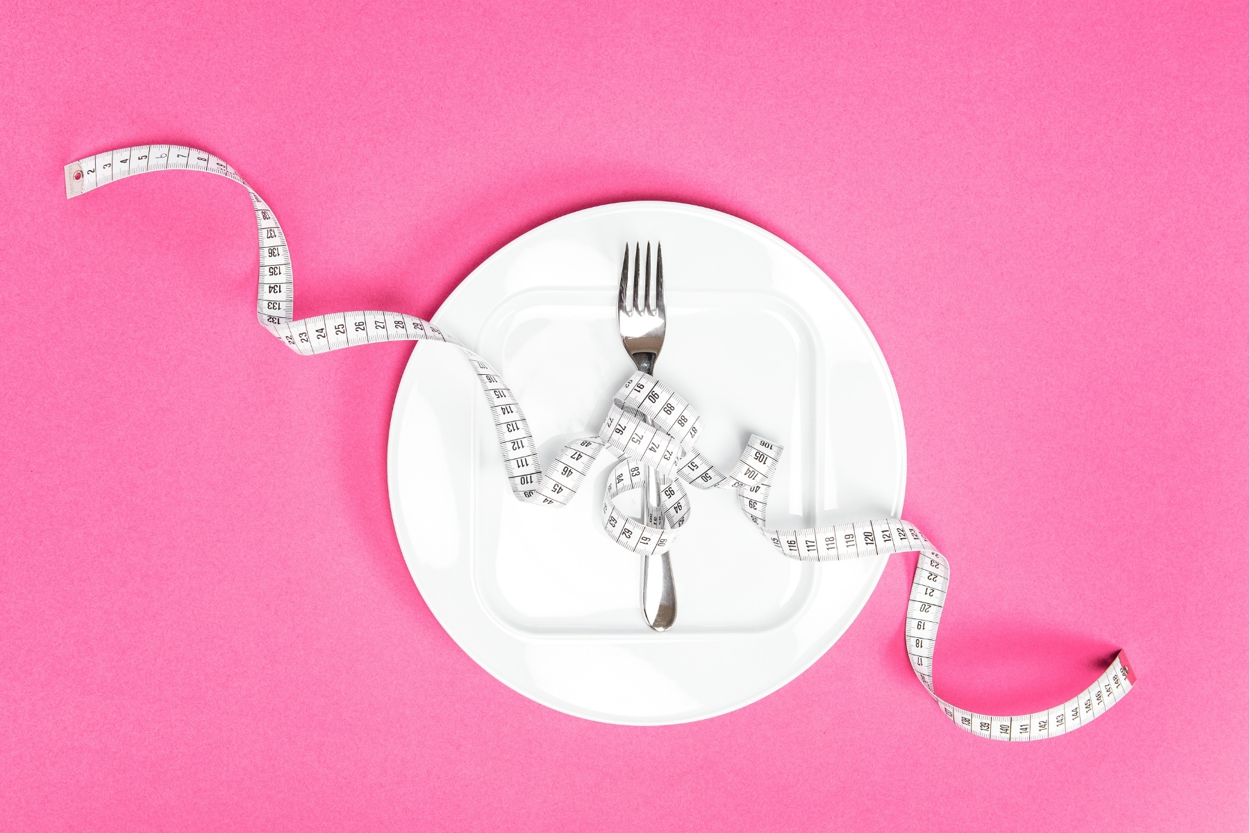 Image representing diet culture and not intuitive eating: a white dinner plate with a fork wrapped in a measuring tape on a pink background.