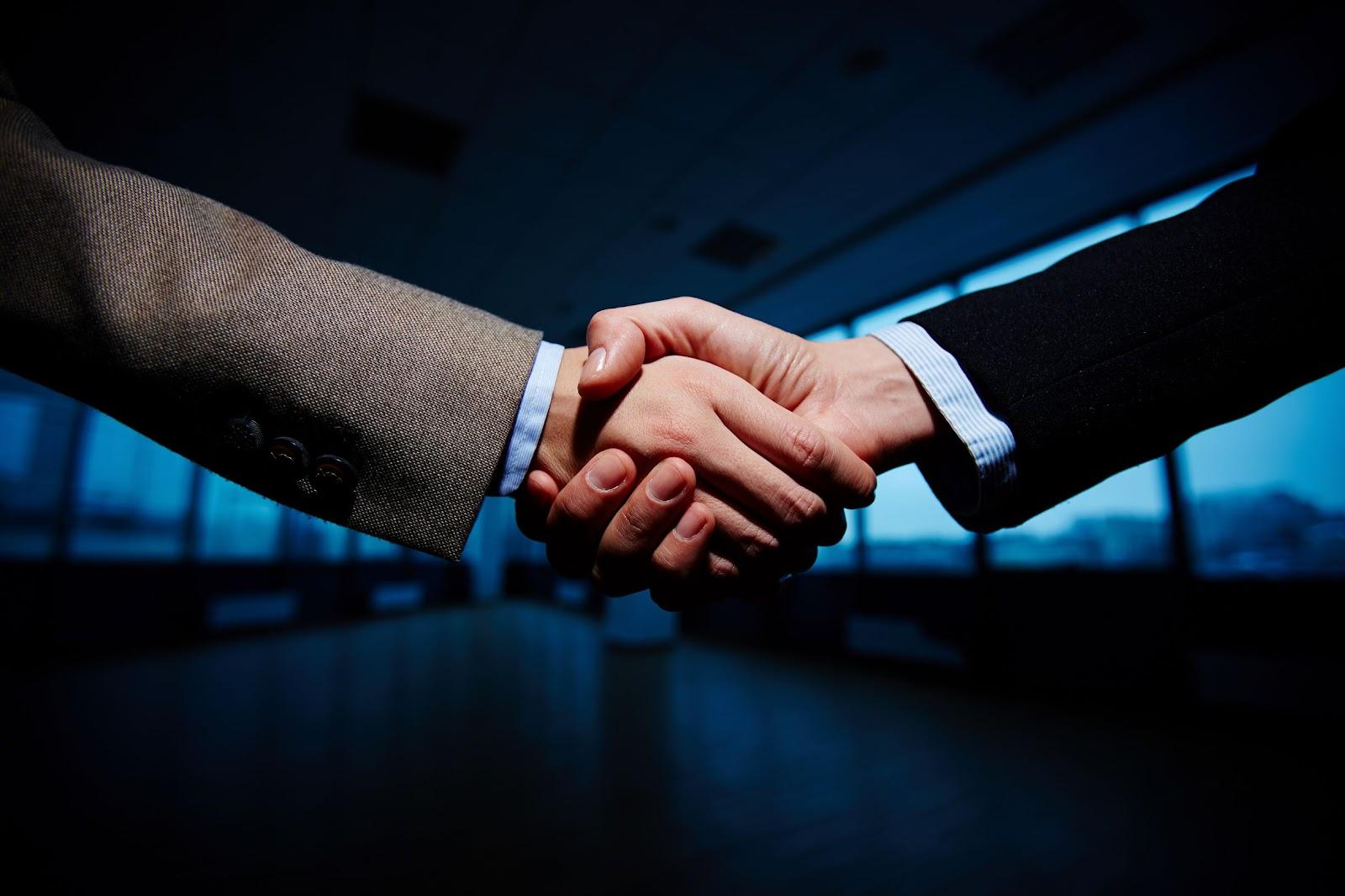 Foto de uma mão masculina apertando uma mão feminina. É possível identificar traje de negócios nos dois braços, representando, assim, a importância da confiança e do conhecimento sobre o que significa backup.