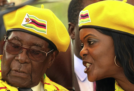 President Robert Mugabe listens to his wife, Grace Mugabe, at a rally of his ruling Zanu-PF in Harare.