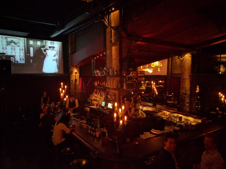 Black and white movies projected on the walls behind industrial bars.
