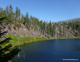Photo: The southwestern rim of the Blue Lake caldera, with the springs along the shoreline