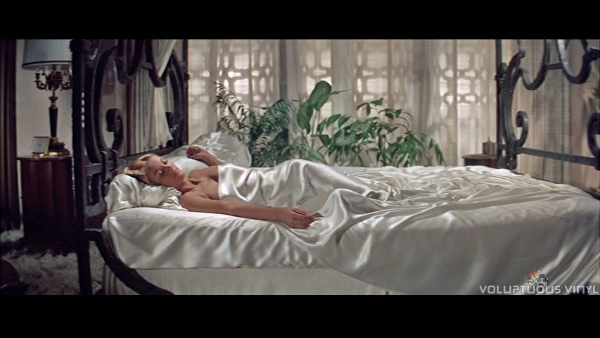 Barbara Bouchet sleeps in the nude under white satin sheets.