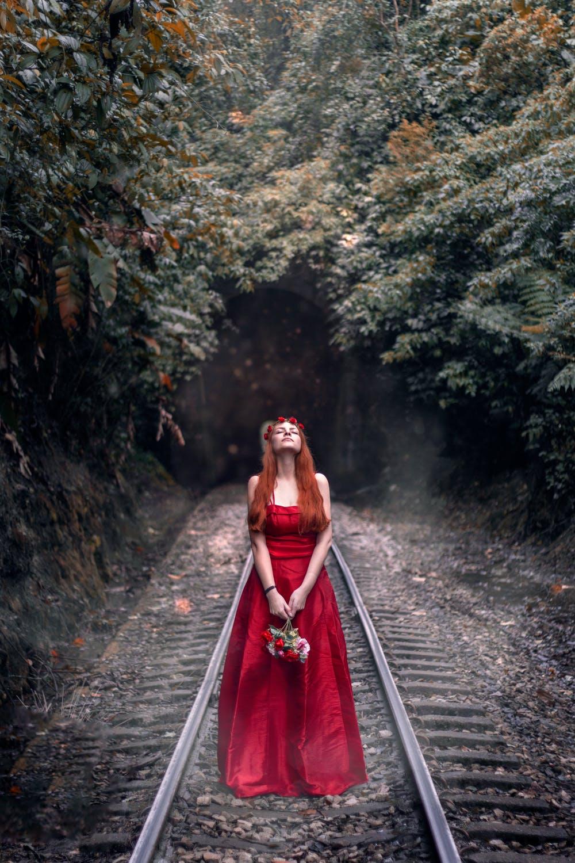 women in red dress on railroad track