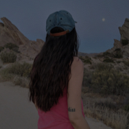Back of woman's head who is looking at the moon coming up over the desert