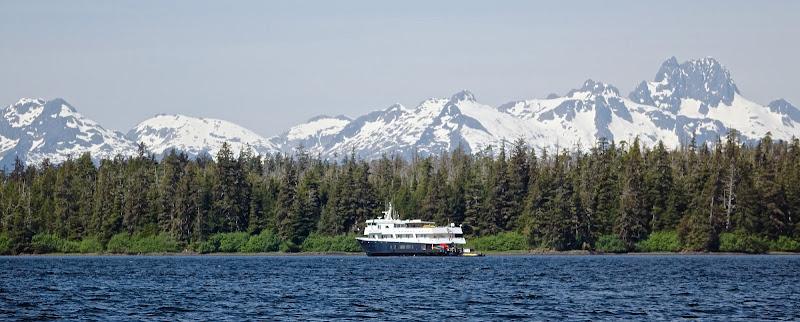 An Un-Cruise Adventures ship sails past glaciers in Alaska.