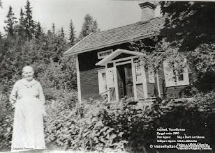 Photo: Asplund. Augusta Persson vid Asplund omkring 1920, huset ligger efter vägen till FlögforsAugusta var mor till Hjalmar Pettersson, kooperativaföreståndaren, bosatt vid Annelund 5-17. Augusta var farmor till Ingemar Persson på Nabben
