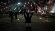 Fireworks explode over a protester with his hands up during a protest against the death in Minneapolis police custody of African-American man George Floyd, in Ferguson, Missouri, US, on May 30 2020.