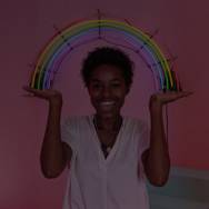 Woman in pink room, pretending to hold neon rainbow light sign that's hung on the wall