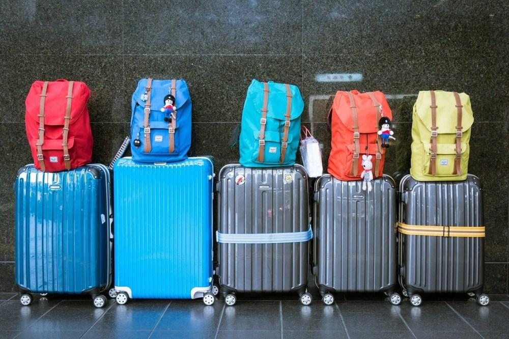 Family of 5's luggage all lined up against wall with colorful backpacks and straps. Learn about Magical Express luggage transfers work from Heyday Travel Company!