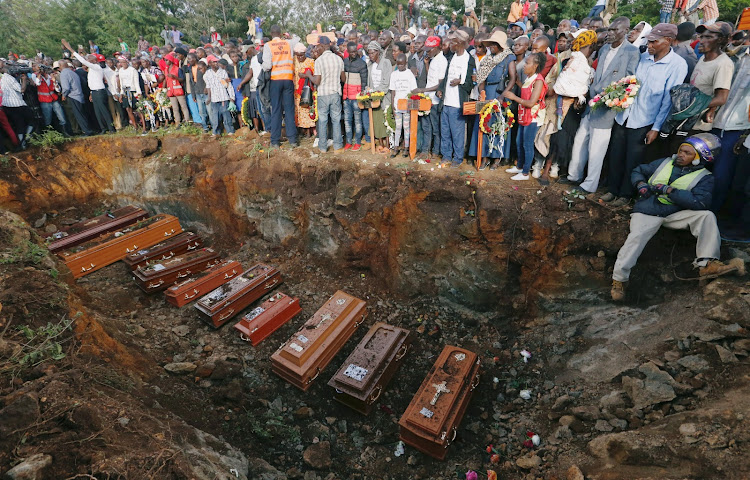 Coffins are lined up in a mass grave during the burial of people killed when a dam burst its walls, overrunning nearby homes, in Solai town near Nakuru, Kenya.