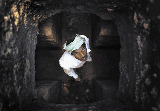 MY WIFE DOES THE WASHING: A worker peers up a chimney at a brick factory in Lalitpur, India, while renovating it