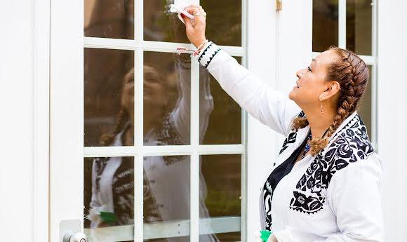 An NDWA-affiliated housecleaner wipes down a window