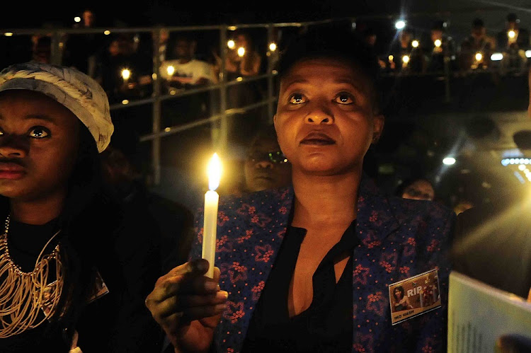 FILE PICTURE: Actress Manaka Ranaka holds up a candle during the memorial service of transgender celebrity and stylist Iko Mash.