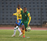 Gladwin Shitolo of Golden Arrows challenges Hlompho Kekana of Mamelodi Sundowns.
