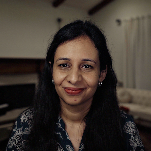 Portrait of Sarah Sirajuddin. She has long black hair and is smiling at the camera.