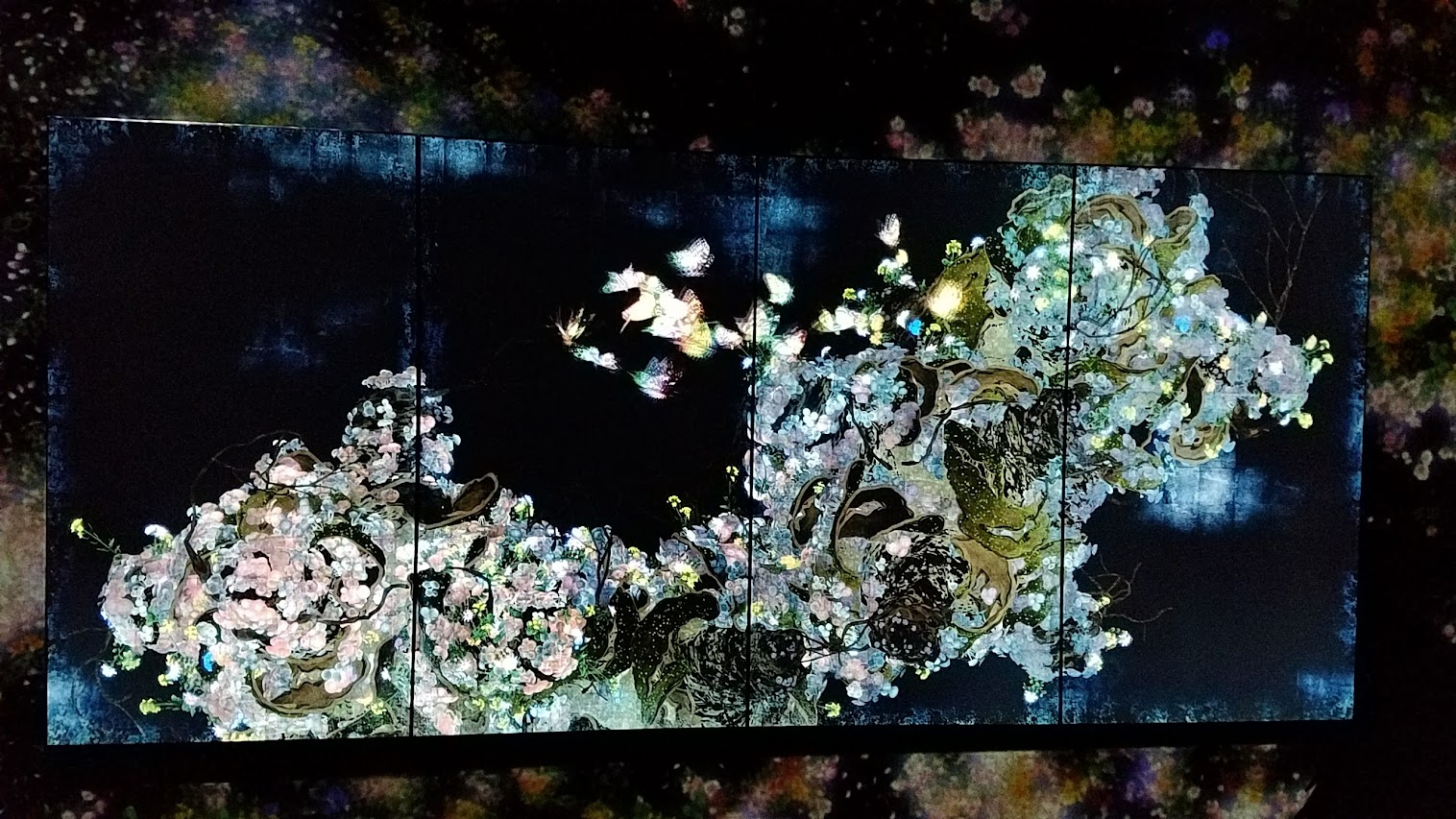 Flutter of Butterflies Beyond Borders as part of Pace Art + Technology exhibit Living Digital Spaces and Future Parks. This was a mode of the TV screen that would swap between Ever Blossoming Life II in turns. For this art piece, butterflies appear on the screen and fly seamlessly into the nearby installation (aka outside the TV screen and into the room walls). It challenges the boundaries between the works. The flight pattern of the butterflies in Flutter of Butterflies Beyond Borders is influenced by the state of the other works, as well as the behavior of the viewers. The butterflies gather in places where flowers bloom in the other works; and if a viewers touches a butterfly, it loses its life.