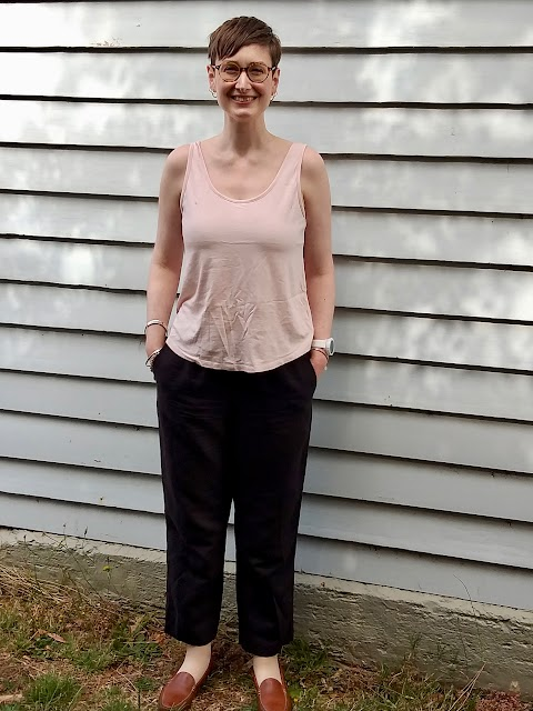 Siobhan stands in front of a blue weatherboard wall. She wears a pink tank top, black elastic waist straight leg linen pants and brown loafers. Her hands are in the pants side pockets and she is smiling.