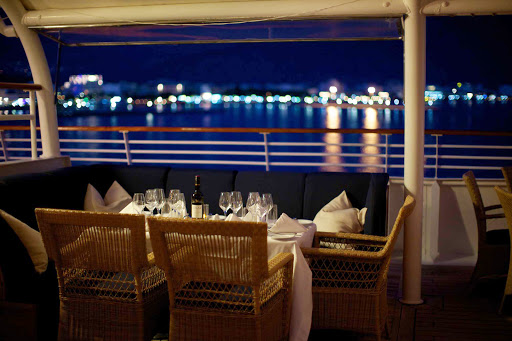 SeaDream-deckdine.jpg - Dine on deck as lights sparkle along the shoreline on a SeaDream cruise.