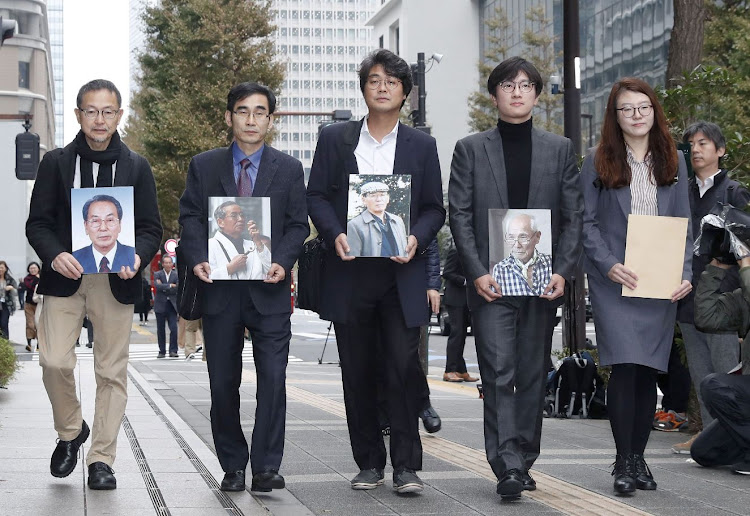 Lawyers and activists hold photos of South Korean plaintiffs who were forced to work for a Japanese firm during World War 2 as they visit Nippon Steel & Sumitomo Metal's headquarters building in Tokyo, Japan, in this photo taken on November 12 2018. Picture: KYODO/VIA REUTERS