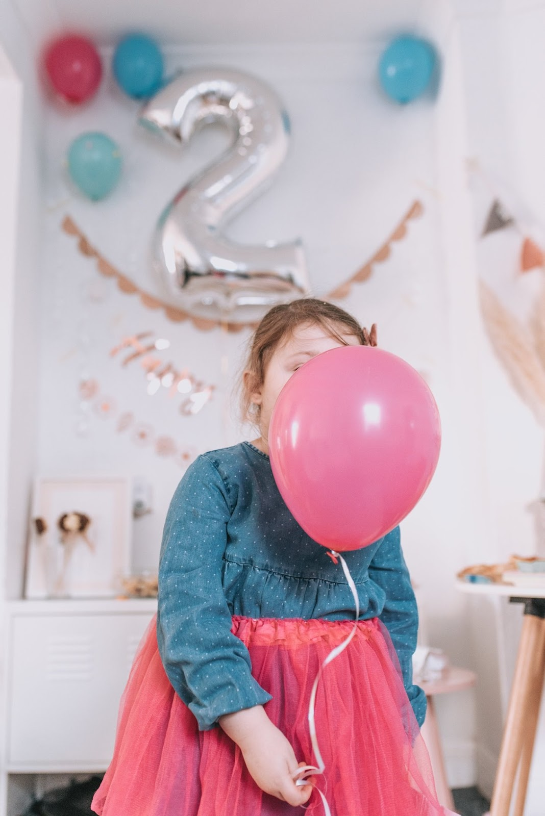 bear and rose gold themed birthday party girl with pink balloon