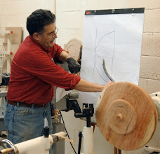 Photo: Clif secured the tenon on the outside bottom and reverse mounted it into a scroll chuck.  Here, on the flip chart, he shows the shape of the bowl and how the shape of the McNaughton cutting blade fits the shape.