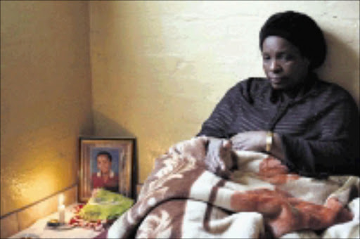 TRAGEDY: Sebenzile Sithole mourns her daughter Thabisile, 13, (framed photo) who was raped and then killed. 18/04/09. Pic. Thuli Dlamini. © Sowetan.
