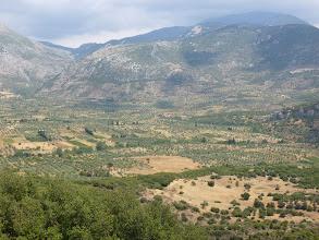 Photo: le monastère domine une plaine de cultures et d'oliviers
