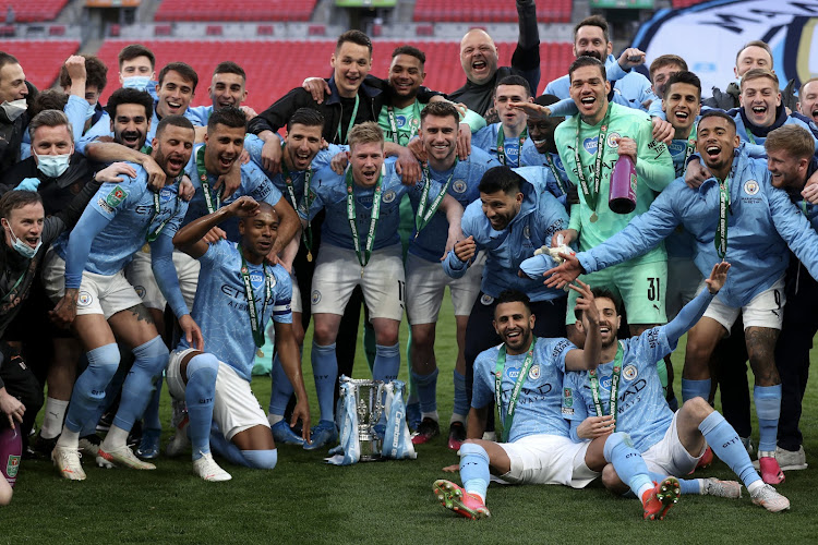 Manchester City players celebrate with the League Cup trophy, their fourth in a row.