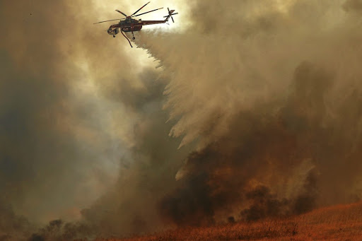 A helicopter drops water on a wind-driven wildfire in Orange, California, on October 9 2017. Picture: REUTERS