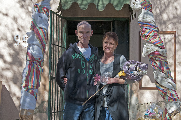 Alph and Jenny Biddulph of Brakpan outside their house with flowers made out of paper and an arch that the bridal couple walked through at their recycled wedding reception.