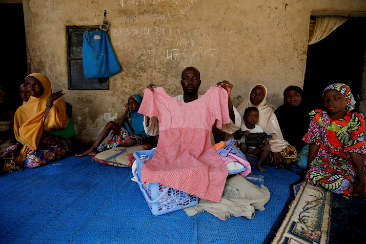 Kachalla Bukar, father of Aisha Kachalla, a missing student of Government Girls Science and Technical College, holds a dress of her daughter in Dapchi, in Yobe, Nigeria.