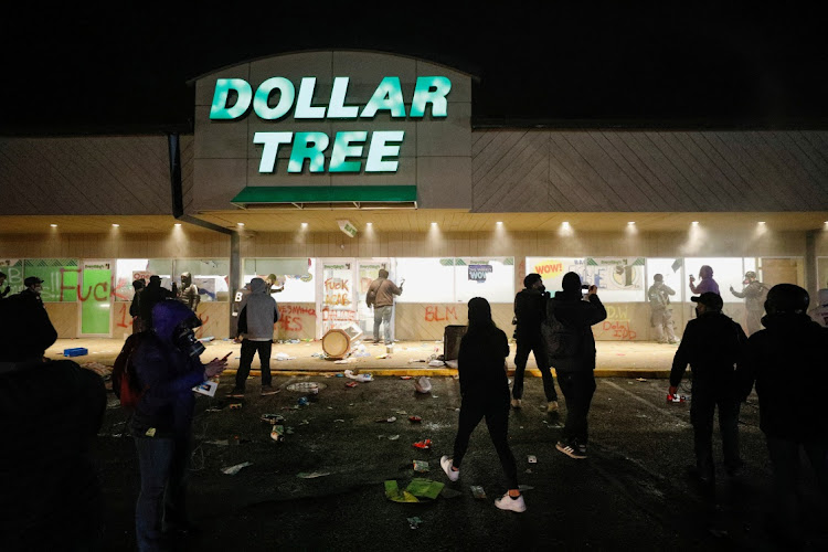 A Dollar Tree store that was looted has its sprinklers turned on as protesters gather outside Brooklyn Center Police Department a day after Daunte Wright was shot and killed by a police officer, in Brooklyn Center, Minnesota, US, on April 12 2021.