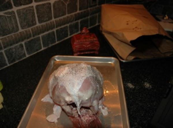 Sprinkle salt and pepper between skin and on top of turkey.