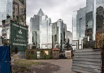 armzalige houten barakken tussen glazen torenflats