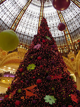 Photo: Monday morning takes us to the Grands Magasins – the big Paris department stores. Here, the tree in the main rotunda of the Galleries Lafayette. An inspection of the well-coiffed locals shows that there are two predominant hair coloring schemes in Paris this year. The first is streaked, especially with prominent auburn highlights; the second is jet black. The latter goes well with the prescribed outfit for the fashionable Parisienne: black boots, black slacks (or ankle-length skirt), black sweater, black scarf (in the round-the-neck European style), black coat, black gloves, and (optional) black hat.
