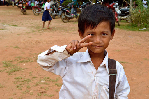 A young boy flashes a V sign, a common gesture for greeting strangers, in Vietnam.