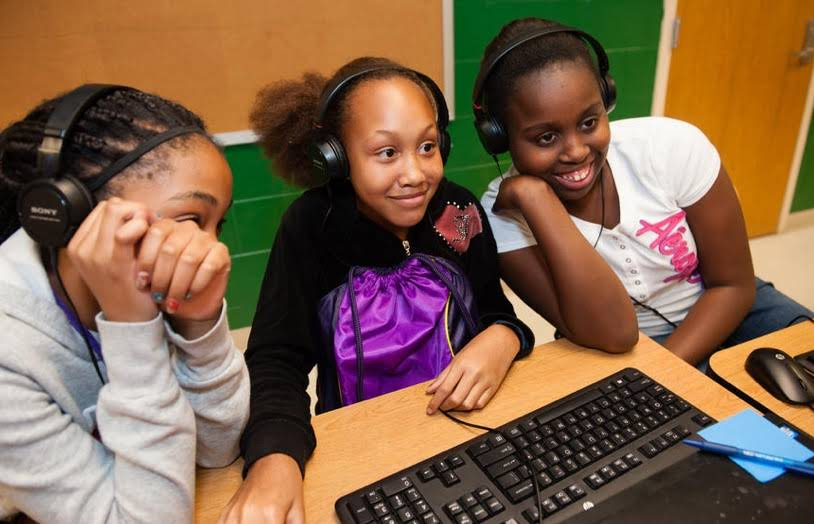 Three smiling young girls wearing headphones working in front of a computer.