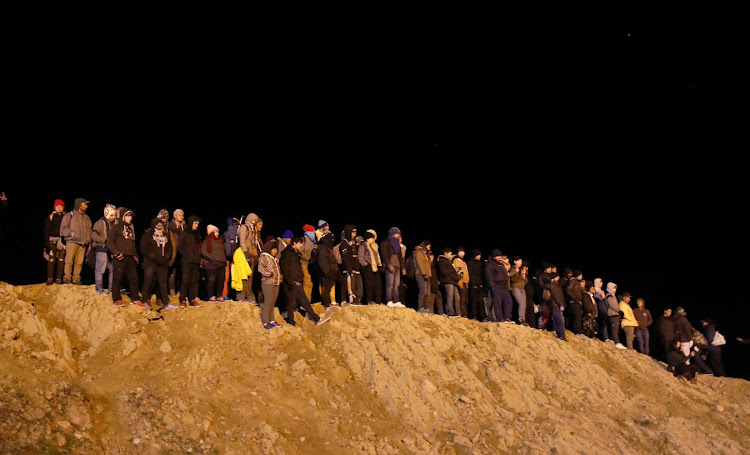 Migrants from Honduras, part of a caravan of thousands from Central America trying to reach the US, stand near the border fence to cross it illegally from Mexico into the US, in Tijuana, Mexico, on January 1 2019. Picture: REUTERS/MOHAMMED SALEM