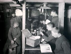 """Photo: Una mañana en el Ritz a mediados del invierno de 1915 . A la izquierda Blackborow lleva un trozo de hielo que será derrido para tener agua.  A la derecha, los científicos trabajando. """""""