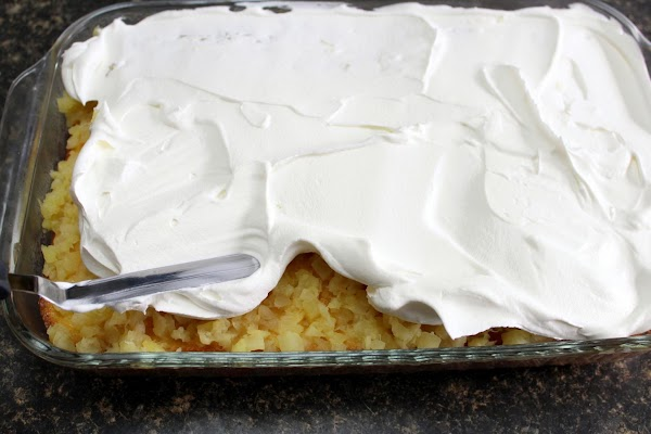 Whipped topping added on top of pineapple.