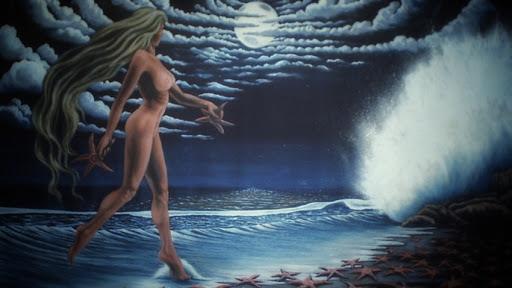 Mujer rubia danzando en la orilla del mar