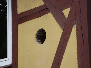 Photo: Grosse Löcher werfen ihre Schatten voraus ;-)  Der Edelstahlkamin ist da und so wurde schon mal von aussen die Bohrung gemacht fürs Ofenrohr. Für mich ganz interessant, da ich nun weiss aus was meine Aussenwand ausser Holzständerwerk ist, nämlich aus Ziegelsteinen. Und dann kommt wie ich vermutet hatte eine Unterlattenkonstruktion und dann sowas wie die Schrankrückwände, also gepresste Pappe beklebt mit Folie bzw. dünnem Holzfurnier.