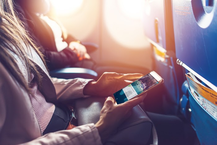 Woman using app on phone on plane