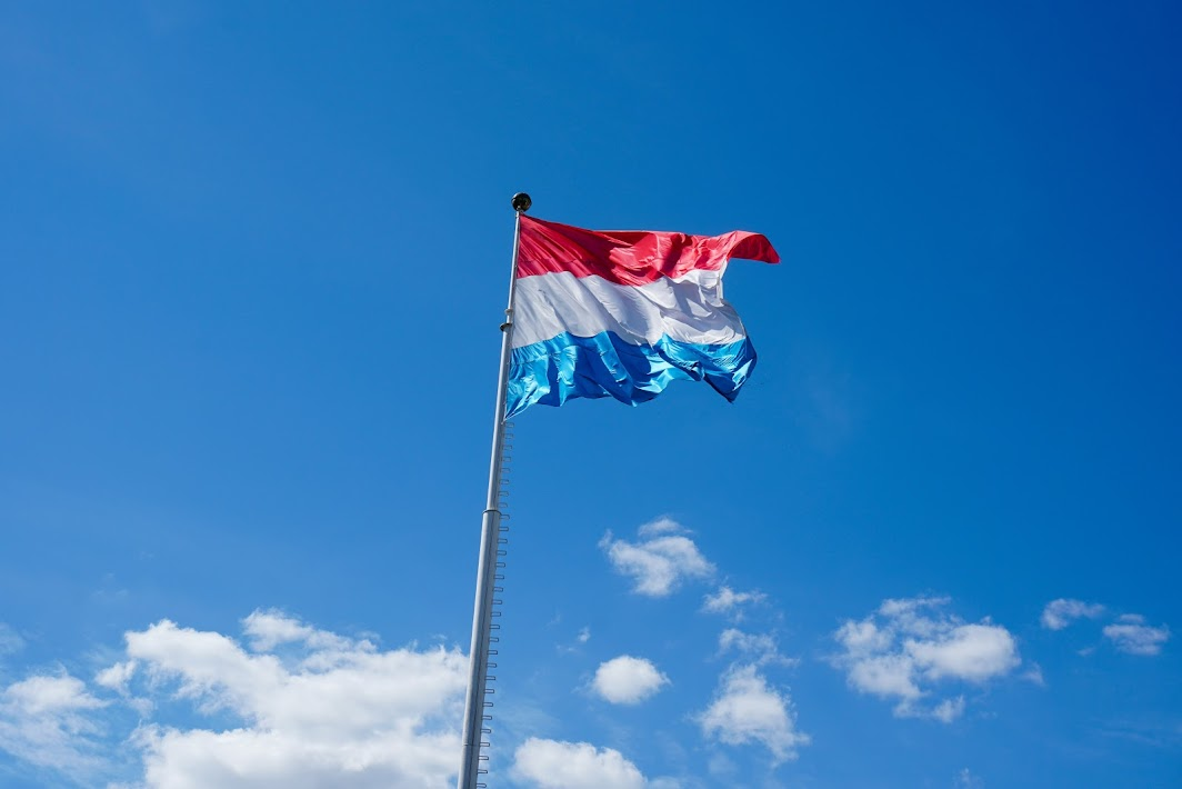 Luxembourgish flag – of red, white and light blue stripes – fluttering in the wind at the top of a flagpole and against a clear blue sky with a few white clouds.